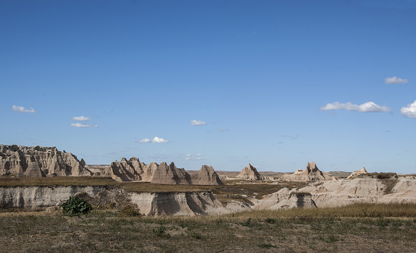 Badlands, S Dakota, National Park, blue skies tiny clouds, interesting geological formations