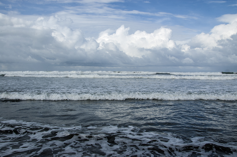 Costa Rica beach scene with clouds and frothy water with waves in background.